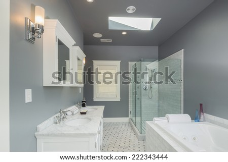 Luxury bathroom with Glass shower and white marble counter tops plus bath top in grey. - stock photo