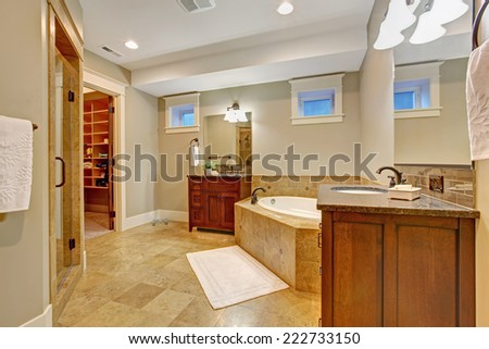 Luxury bathroom with granite tile trim. Spacious bathroom with corner bath tub, two vanity cabinets and walk in closet - stock photo