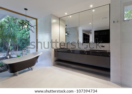 Luxury bathroom with mirror, sink and classic bathtub - stock photo