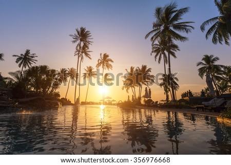 Luxury beach hotel, silhouette of palm trees, swimming pool, an beautiful sunset - stock photo