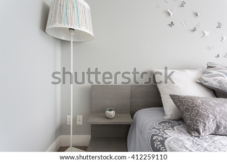 Luxury bedroom. Contemporary design with butterflies on the wall, pillows and lamp. Nice and cozy accommodations. Hotel or resort room.  - stock photo