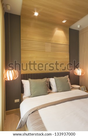luxury bedroom decorated with wood from headboard to ceiling. - stock photo