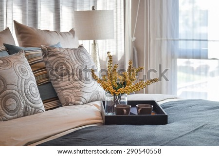 luxury bedroom interior design with decorative tea set and striped pillows on bed - stock photo