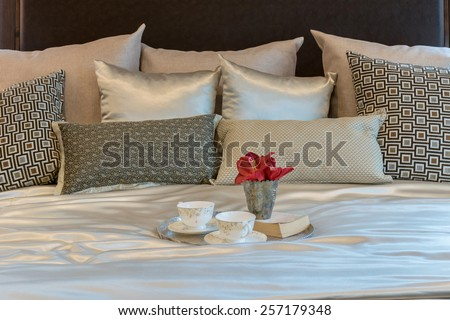luxury bedroom interior with brown pattern pillows and decorative tray of flower on bed - stock photo