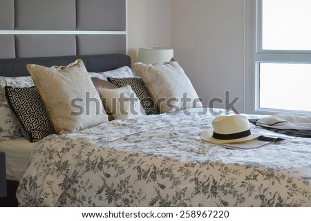 luxury bedroom interior with flower pattern pillows and decorative table lamp - stock photo