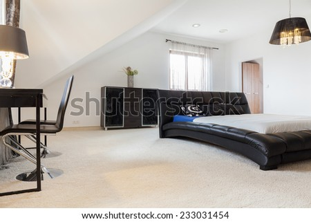 Luxury bedroom interior with leather double bed - stock photo