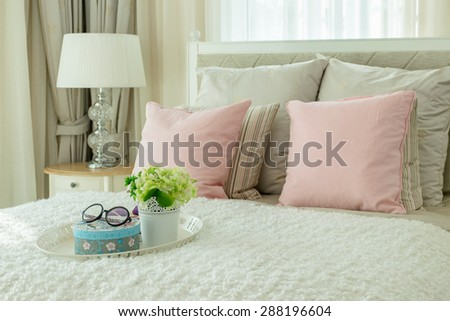 luxury bedroom interior with pink pillows and white tray of flower on bed - stock photo