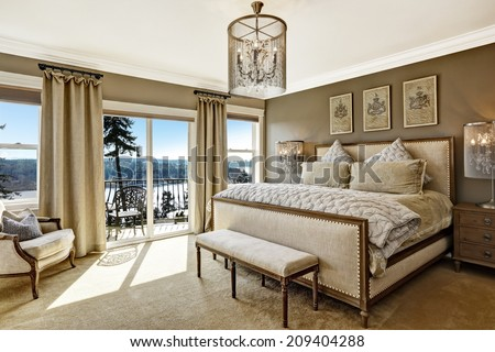 Luxury bedroom interior with rich furniture and scenic view from walkout deck - stock photo