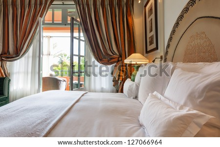 Luxury bedroom that opens with French doors onto a terrace.  King bed with white linens and pillows. - stock photo