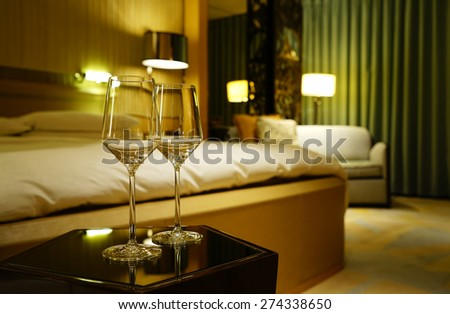 Luxury bedroom with empty red wine glasses as background.