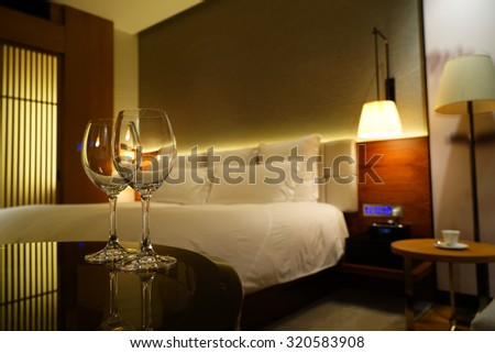 Luxury bedroom with empty red wine glasses as background. - stock photo