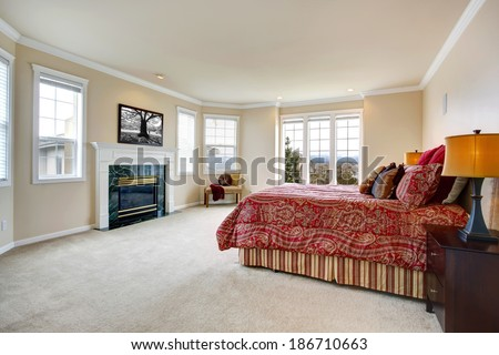 Luxury bedroom with gentle ivory walls, french windows and fireplace. Furnished with bed, nightstand and ottaman
