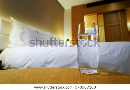 Luxury bedroom with glass of water as background.