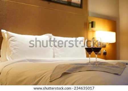 Luxury bedroom with red wine as background.