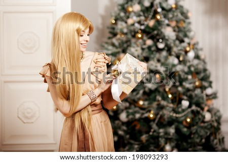 Luxury blonde in interior New Year. Young beautiful trendy girl celebrating Christmas. The friendly woman