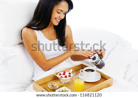 luxury breakfast in bed with coffee and croissant and healthy fruit for attractive young woman - stock photo