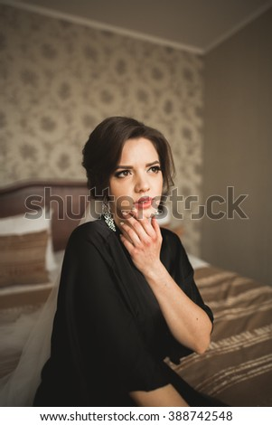 Luxury bride in black robe posing while preparing for the wedding ceremony