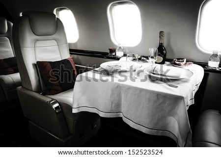 Luxury Business Jet Interior with served table and leather chair - stock photo