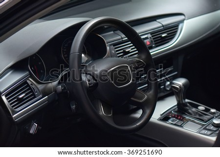 luxury car black leather and brushed aluminium interior inside view with automatic transmission, GPS screen, steering multifunctional wheel, indicators, climatisation dashboard close up. - stock photo