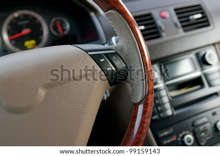 luxury car interior with wooden steering wheel close up