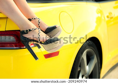 Luxury car travel concept background. Woman feet against a luxury car. Summer vacations concept.  - stock photo
