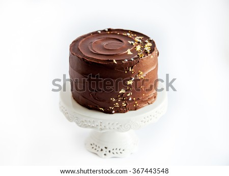 Luxury chocolate cake with edible gold glitter on white cake stand. Isolated on white background.  - stock photo