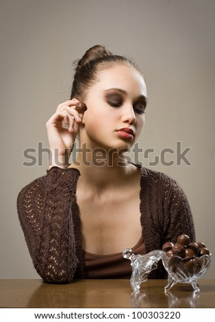 Luxury chocolate, stunning young brunette woman with bonbons. - stock photo