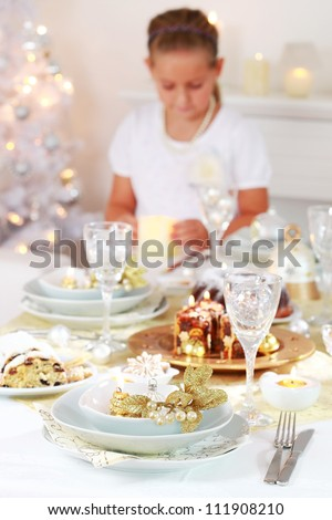 Luxury Christmas place setting with helping child in background - stock photo