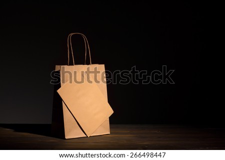 Luxury classic shopping bag and envelope made of craft paper presented on aged wood