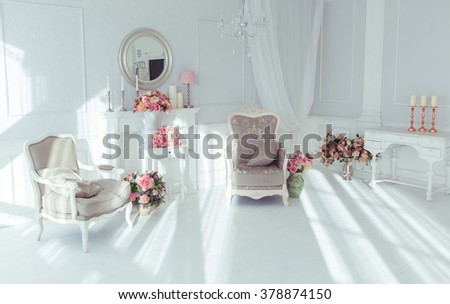 luxury clean bright white interior. a spacious room with sunlight and flowers in vases