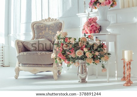 luxury clean bright white interior. a spacious room with sunlight and flowers in vases, - stock photo