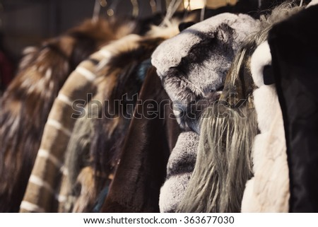 Luxury clothes and furs in a retail fashion store. - stock photo