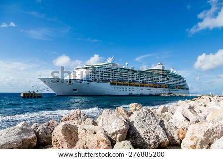 Luxury cruise ship beyond rock sea wall in Curacao - stock photo