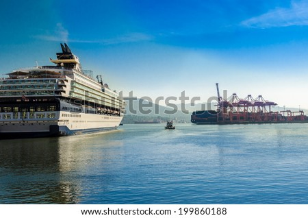 Luxury cruise ship from the stern side sailing at the inlet ( to the harbor ) with the container port terminal on starboard ( right ) side. Vancouver, Canada. - stock photo