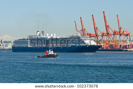 Luxury cruise ship sailing ( arriving to ) from port. With container terminal and tug boat as a background. Vancouver. Canada. - stock photo