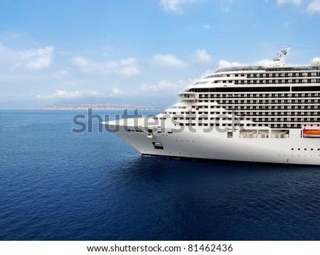Luxury cruise ship sailing from port. - stock photo