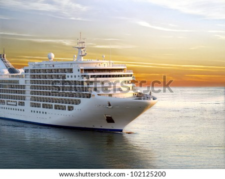 Luxury cruise ship sailing from port on sunset - stock photo