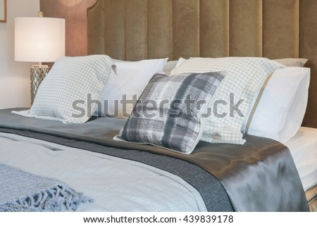 Luxury decorative style bedroom with checked pattern pillows on bed - stock photo