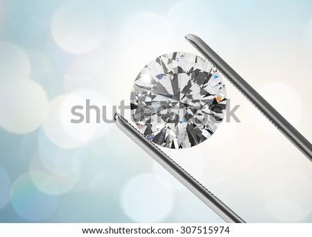 Luxury diamond in tweezers closeup with bright bokeh background - stock photo