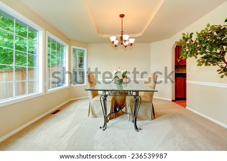 Luxury dining room with french window, ivory walls with white moldings and elegant dining table set.