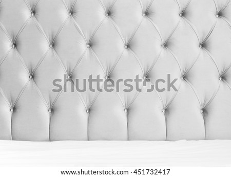 Luxury empty bedroom interior background, soft gray headboard and white bedding sheets on wide double bed
