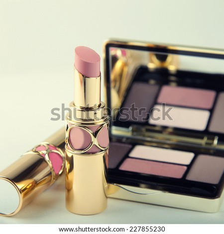 Luxury eyeshadow palette with mirror and lipsticks in pink and beige colors. Selective focus, instagram effect, square toned image - stock photo