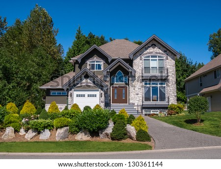 Luxury family house with landscaping and blue sky background. Canada. - stock photo