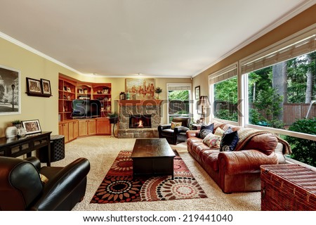 Luxury family room with cozy stone trimmed fireplace. Rich leather couch and armchair create comfort atmosphere - stock photo