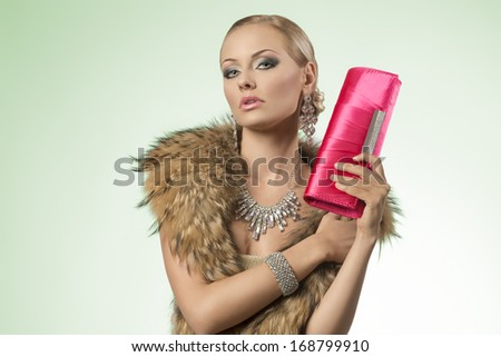 luxury fashion portrait of very sensual blonde girl with aristocratic look posing with fur collar, bright jewelery and elegant small bag in the hand   - stock photo