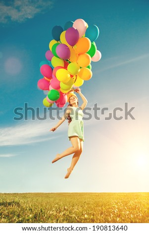 Luxury fashion stylish woman with balloons in hand on the field against the sky and  the sun in long dress  - stock photo