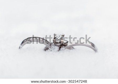 Luxury, fashion wedding three rings of gold, platinum, silver and precious stones, jewel of snow outdoors for the bride and groom on their wedding day. Wedding ceremony in the winter - stock photo