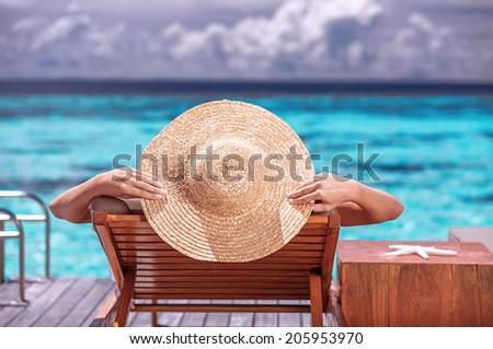 Luxury female tanning on the beach, wearing big stylish hat, enjoying beautiful seascape, summer travel and tourism concept - stock photo