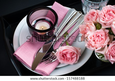 Luxury festive table setting with pink roses, candles and shiny new cutlery on black background isolated - stock photo
