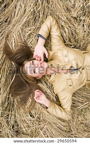 Luxury girl laying in hay - stock photo